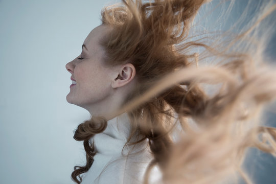 Profile portrait wind blowing through long, curly red hair of Caucasian woman with eyes closed