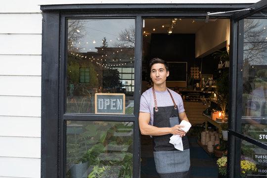 Pensive male shop owner standing in doorway looking away in anticipation
