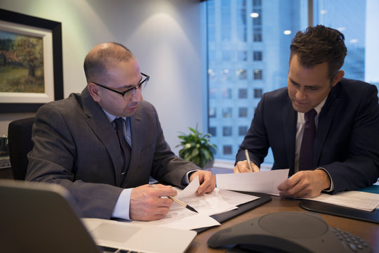 Male lawyers reviewing and signing contract in conference room