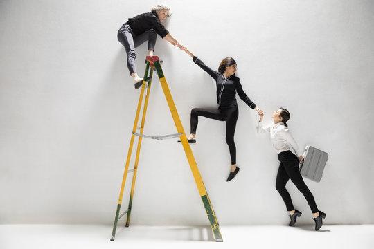 Businesswomen holding hands, helping lift each other on ladder
