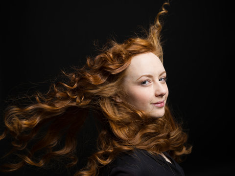 Portrait confident woman with wind blowing long curly red hair against black background