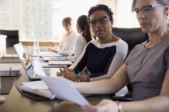 Female lawyers discussing paperwork at laptop in conference room meeting