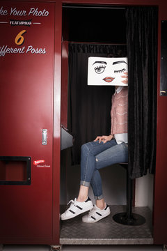 Portrait young woman holding winking face drawing in photo booth