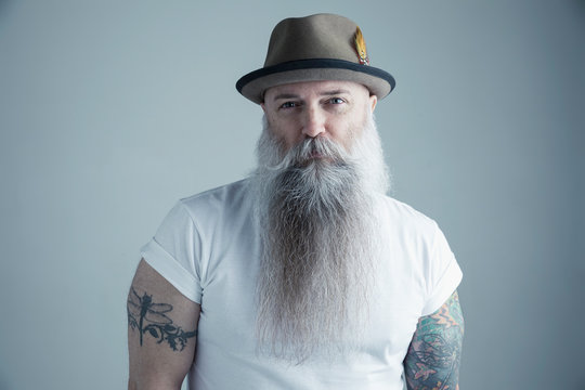 Portrait confident Caucasian male hipster with long gray beard and arm tattoos wearing fedora