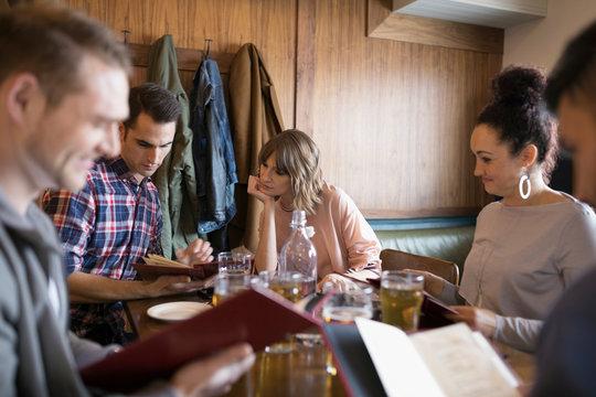 Friends looking at menus at bar table