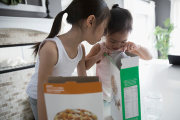 Sisters opening and peering inside cereal box in kitchen