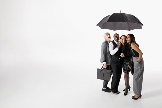 Smiling business people sharing umbrella against white background
