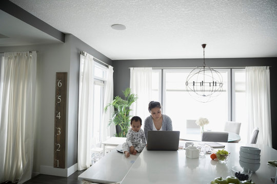 Toddler son playing next to mother working at laptop in kitchen