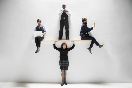 Businesswoman balancing businessmen overhead against white background