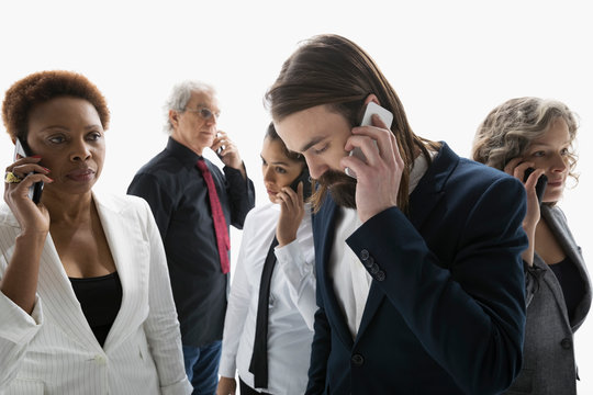 Business people talking on cell phones against white background