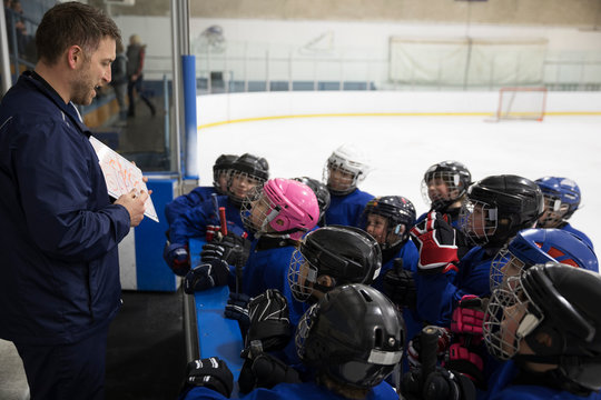 Boy and girl ice hockey players watching coach with clipboard on ice hockey rink