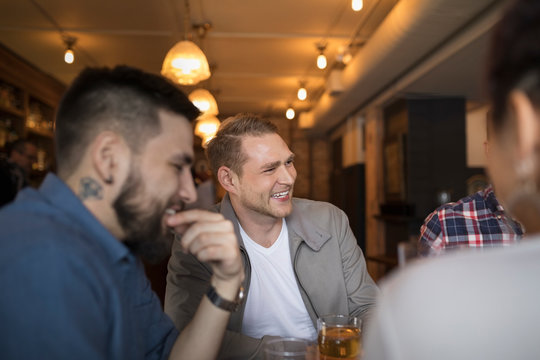 Man laughing with friends and drinking beer in bar