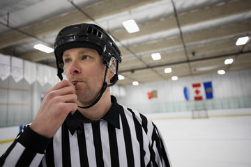 Male ice hockey referee blowing whistle on ice hockey rink