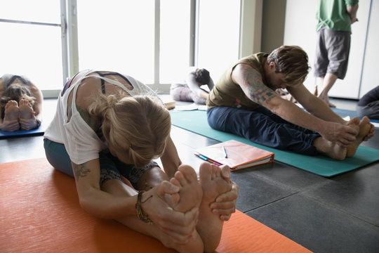 Woman practicing yoga seated fold in yoga class studio