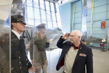 Senior male war veteran saluting Naval officer exhibit in war museum hangar