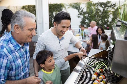 Multi-generation family barbecuing at grill on patio