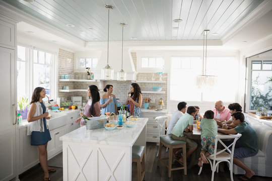 Family and friends eating and drinking in beach house kitchen