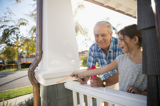 Grandfather and granddaughter blowing bubbles on summer porch