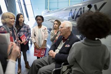 War veteran in wheelchair talking to students on field trip in Naval war museum hangar
