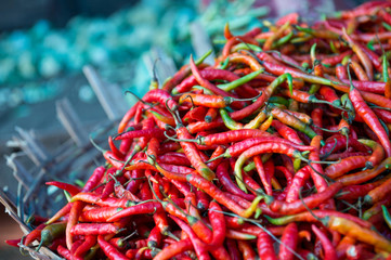 Pile of fresh fiery red hot chili peppers on display in rustic basket at an outdoor vegetable market in Mysore India
