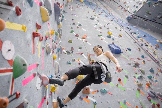 Woman climbing indoor rock wall