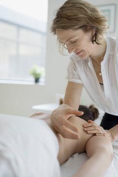 Female masseuse massaging woman on spa massage table