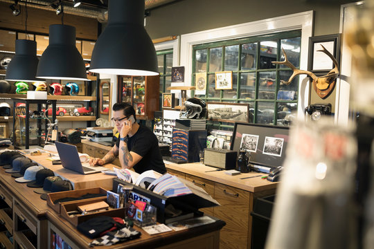 Motorcycle shop owner working at laptop and talking on cell phone behind counter