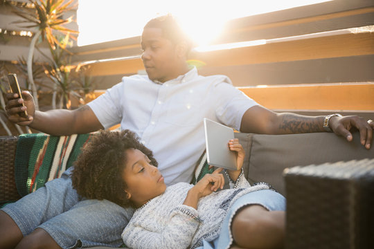 African American father and daughter using digital tablet and smart phone on sunny deck sofa