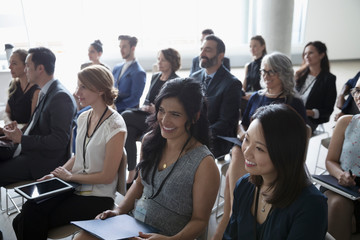Smiling businesswomen listening in conference audience