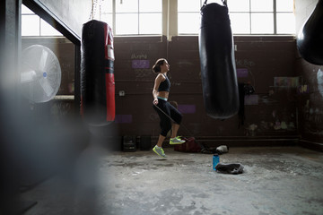 Female boxer jumping rope behind punching bags in gym