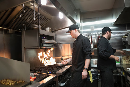 Line cooks preparing food, sauteing at stove in restaurant kitchen