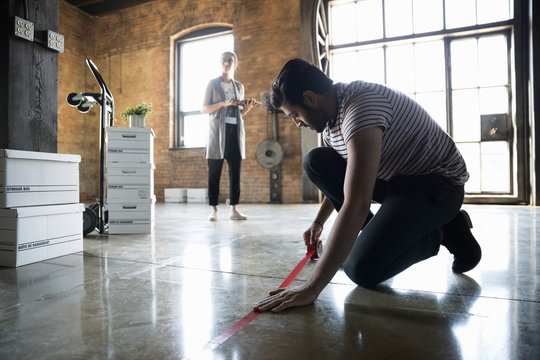 Businessman with tape measure measuring floor in new industrial office