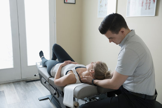 Male physiotherapist examining neck of woman on clinic examination table