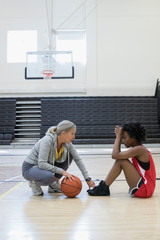 Female coach coaching basketball player in college gymnasium