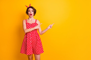 Portrait of astonished crazy girl promoter point index finger copyspace indicate ads incredible promotion impressed scream wow omg wear retro style skirt isolated yellow color background