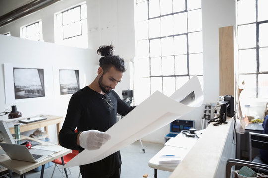 Male photographer examining large photograph print in art studio