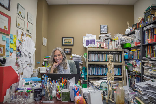 Portrait smiling female college science professor working at laptop in messy office