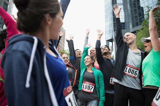 Enthusiastic runners cheering with arms raised before marathon