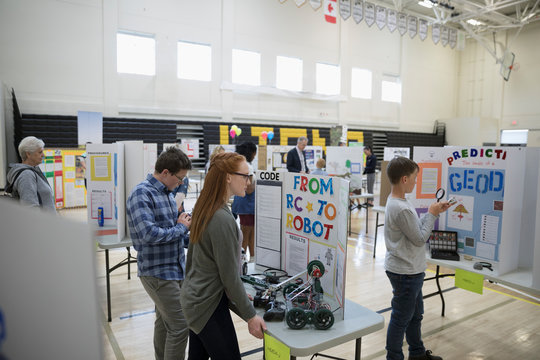Middle school students looking at science projects at science fair