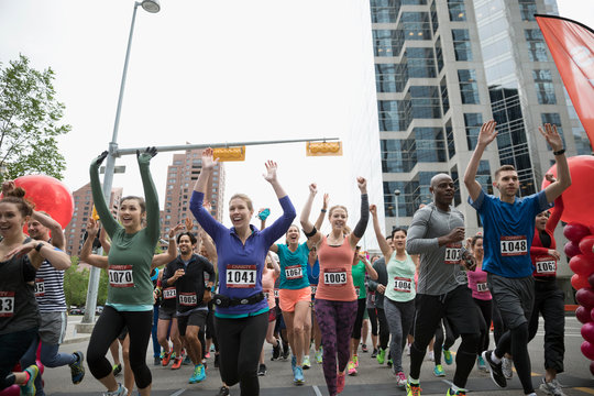 Marathon runners running and cheering with arms raised on urban street