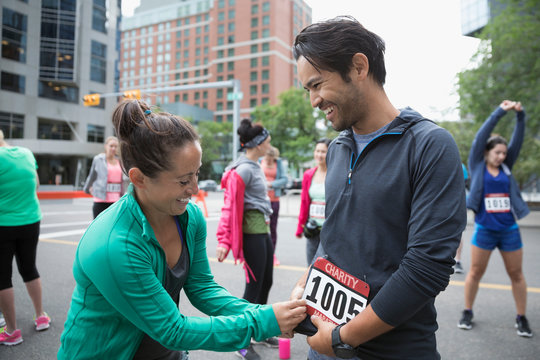 Wife helping smiling husband put on marathon bib on urban street