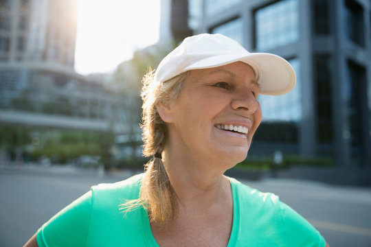 Smiling mature female runner wearing baseball cap on urban street