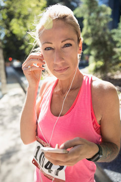 Portrait smiling, confident mature female marathon runner listening to music with earbud headphones and mp3 player