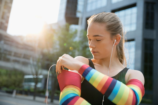 Teenage girl runner wearing rainbow compression arm sleeves, listening to music with mp3 player and earbud headphones