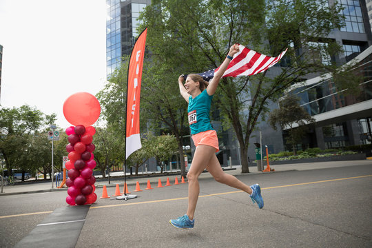 Female marathon runner running with American flag, crossing finish line