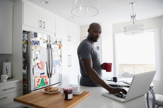 Mature African American man drinking coffee and using laptop at kitchen counter