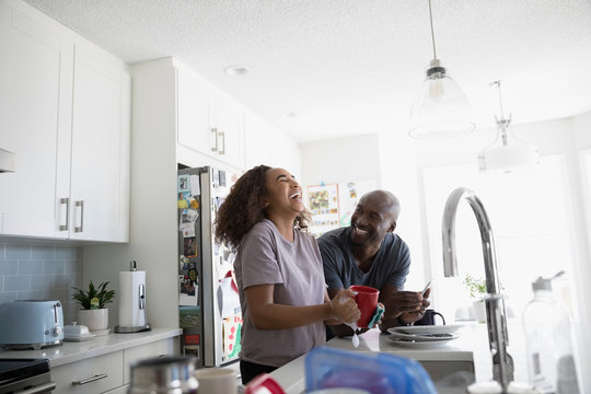 Father and teenage daughter laughing, doing dishes in kitchen