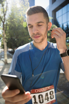 Young male marathon runner listening to music with earbud headphones and mp3 player