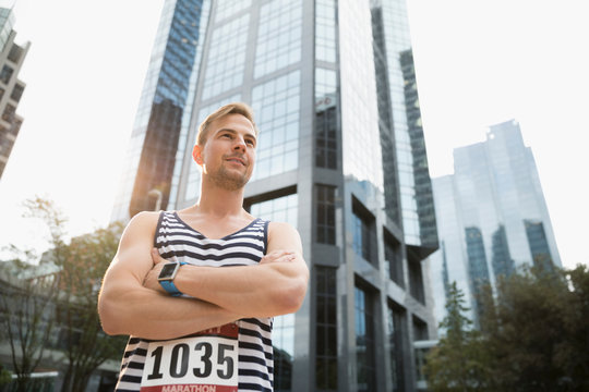 Portrait confident male marathon runner in striped tank top standing below urban highrise building