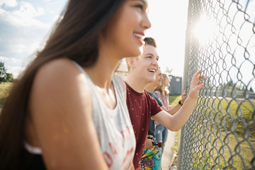 Smiling teenage friends watching game at sunny park fence